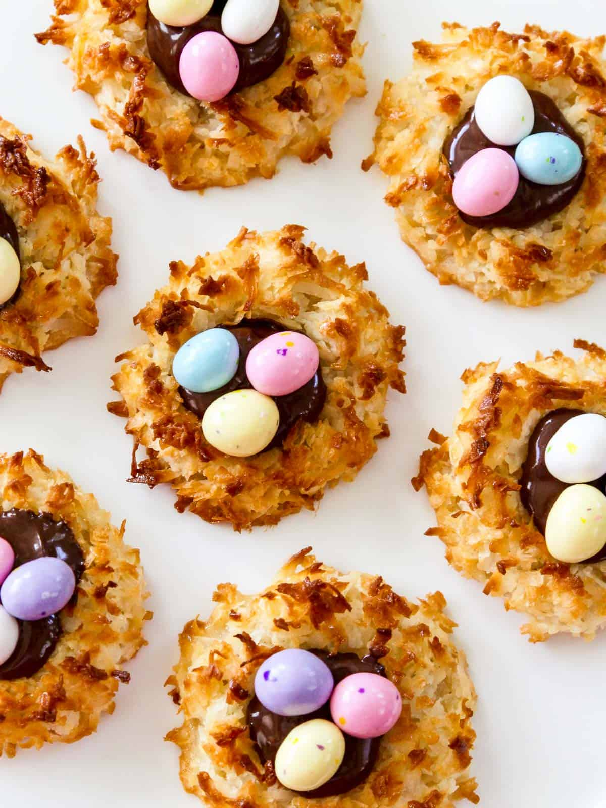 A white plate filled with Easter coconut macaroons decorate with chocolate eggs.