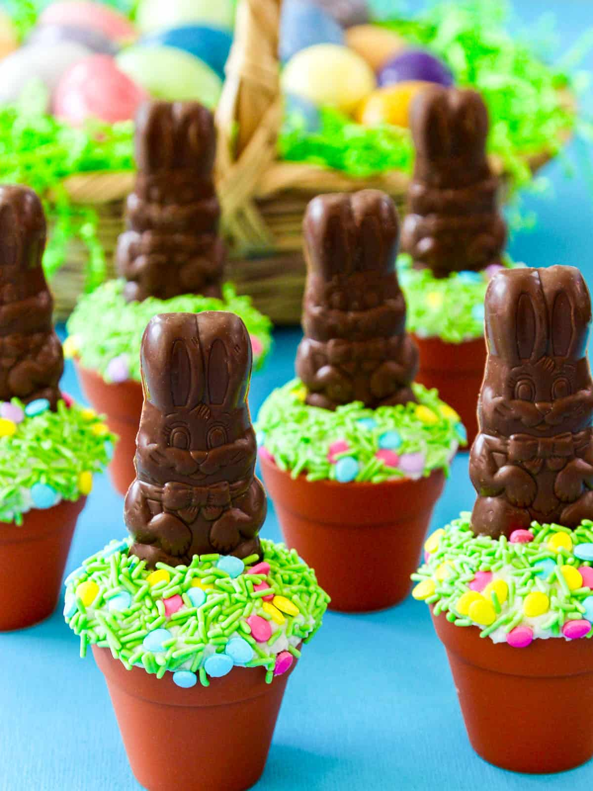 Six Easter cupcakes with milk chocolate bunnies and green sprinkles.