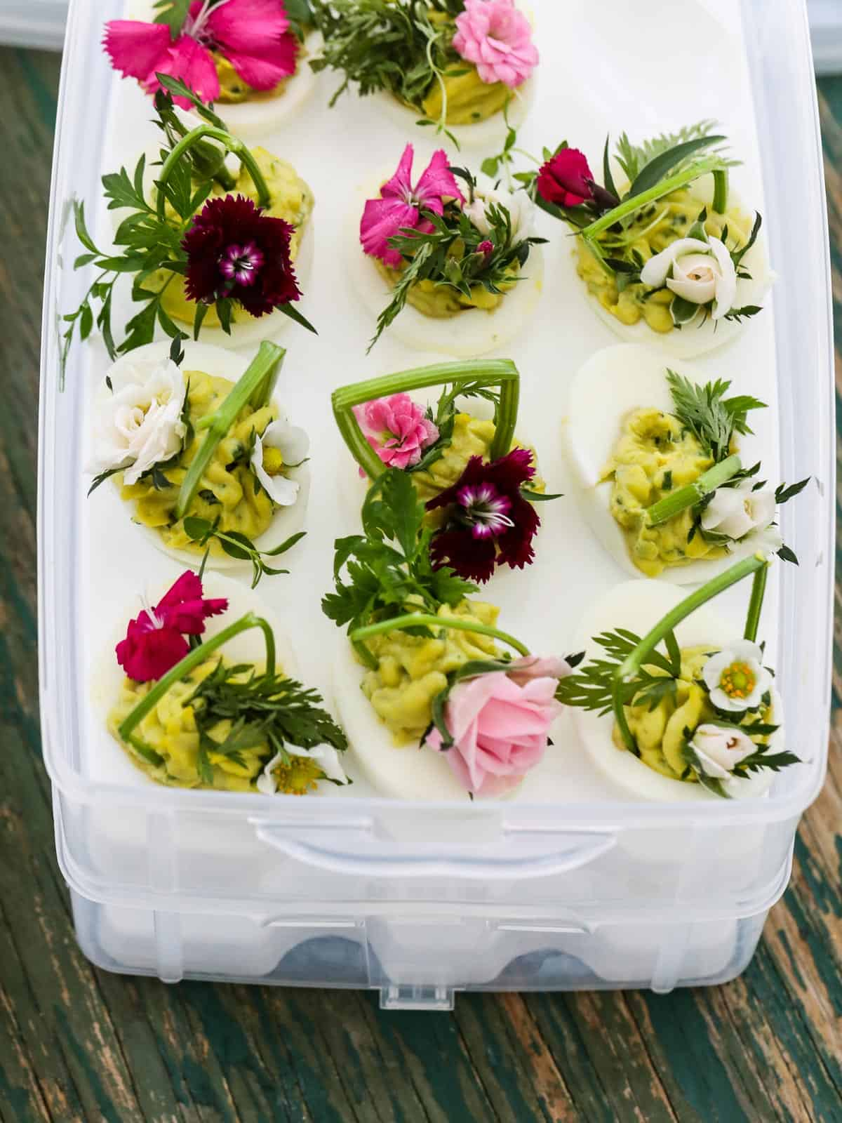 A plastic box designed to carry deviled eggs filled with Easter deviled eggs to take to a party.