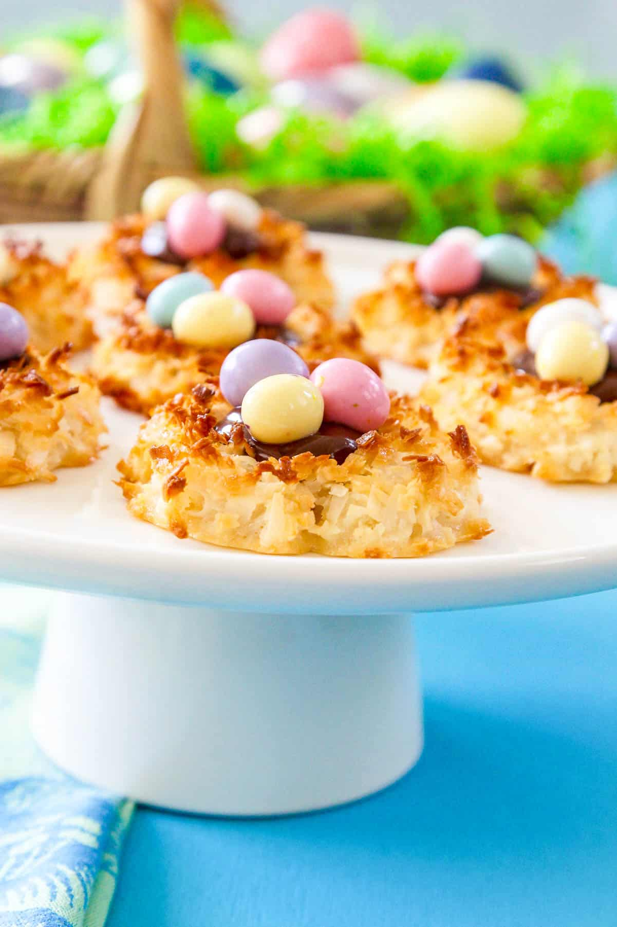A white round platter of bird's nest coconut macaroon cookies topped with chocolate and 3 colorful egg candies.