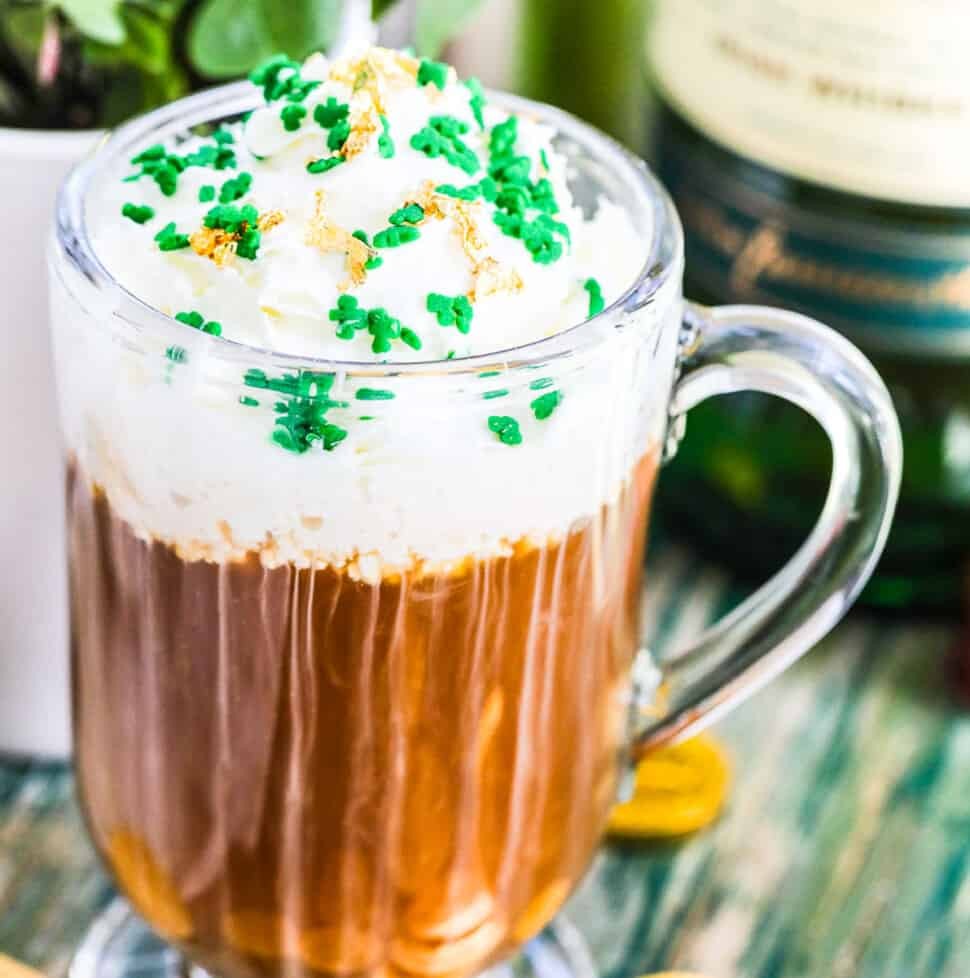 A glass mug with Irish Coffee on a vintage green table topped with green sprinkles and edible gold.