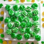 A square white plate with green oreos decorated with shamrock sprinkles.