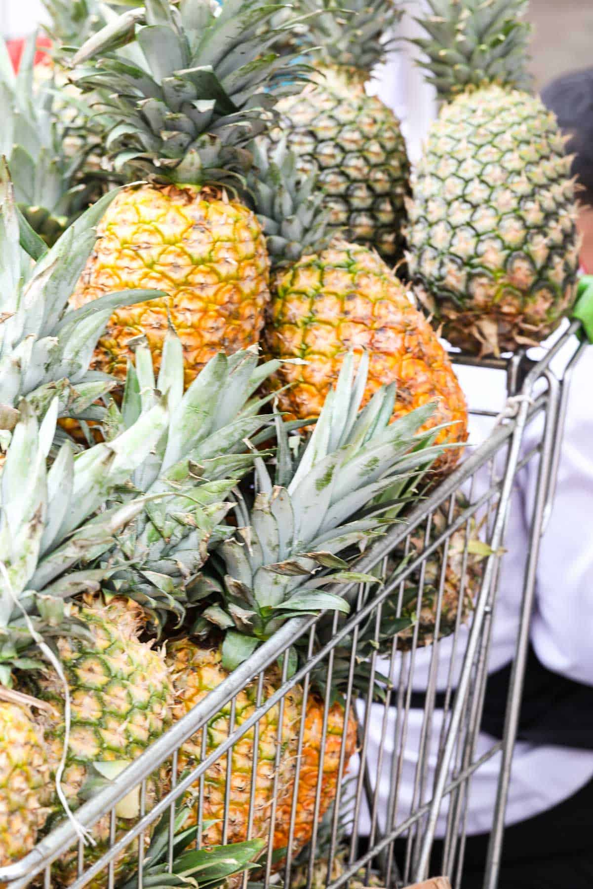 A steel grocery cart filled with fresh ripe whole pineapples in a market.