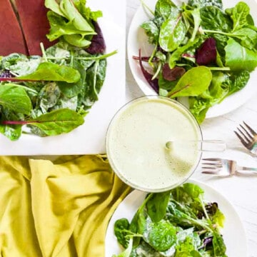 A white table with plates of green salad tossed in Green Goddess Dressing with a green napkin and utensils.