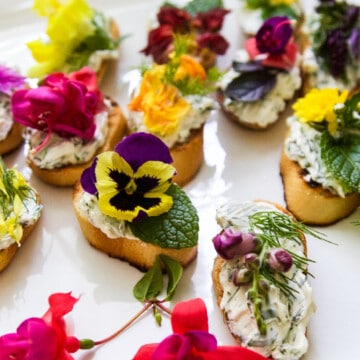 A white platter with crostini recipe topped with edible flowers and herbs.