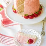 A freshly baked and decorated strawberry cake with real strawberries as decorations.