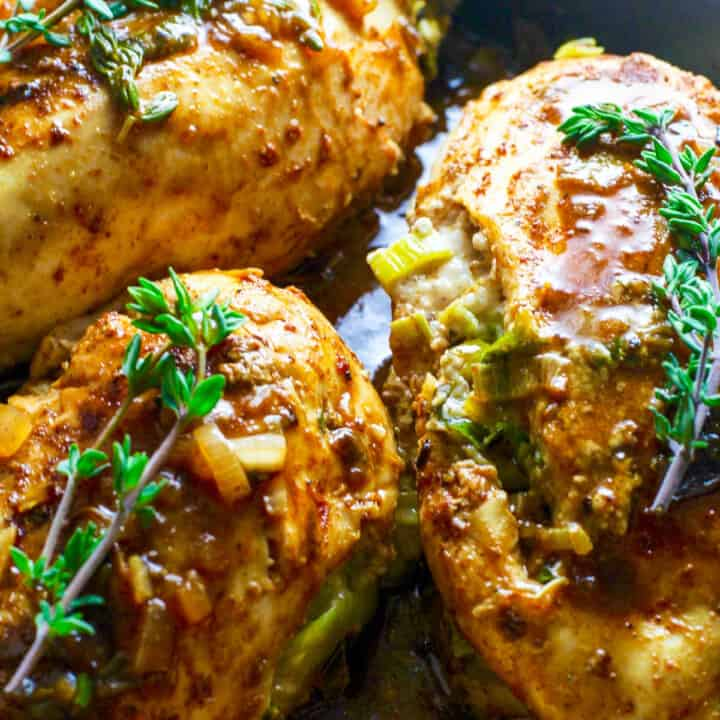 Cooked Gorgonzola Stuffed Chicken in pan sauce garnished with fresh thyme.