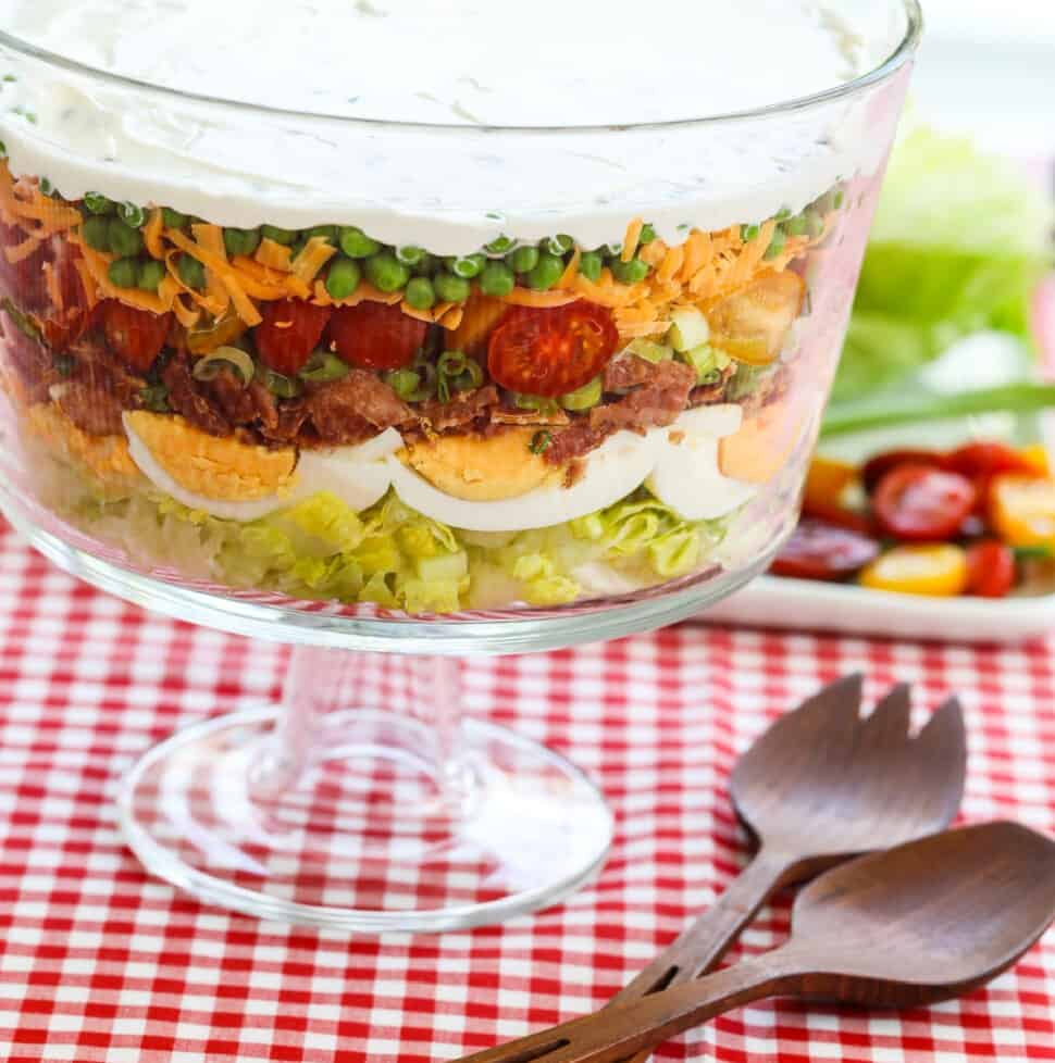 A glass trifle dish filled with 7 Layer Salad full of colorful ingredients.
