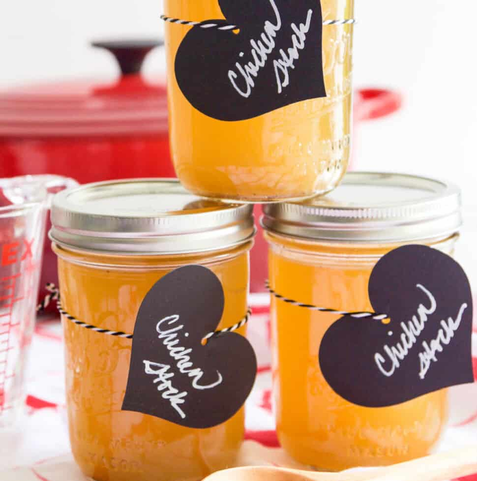 3 small Mason jars filled with chicken stock and black heart shaped labels.