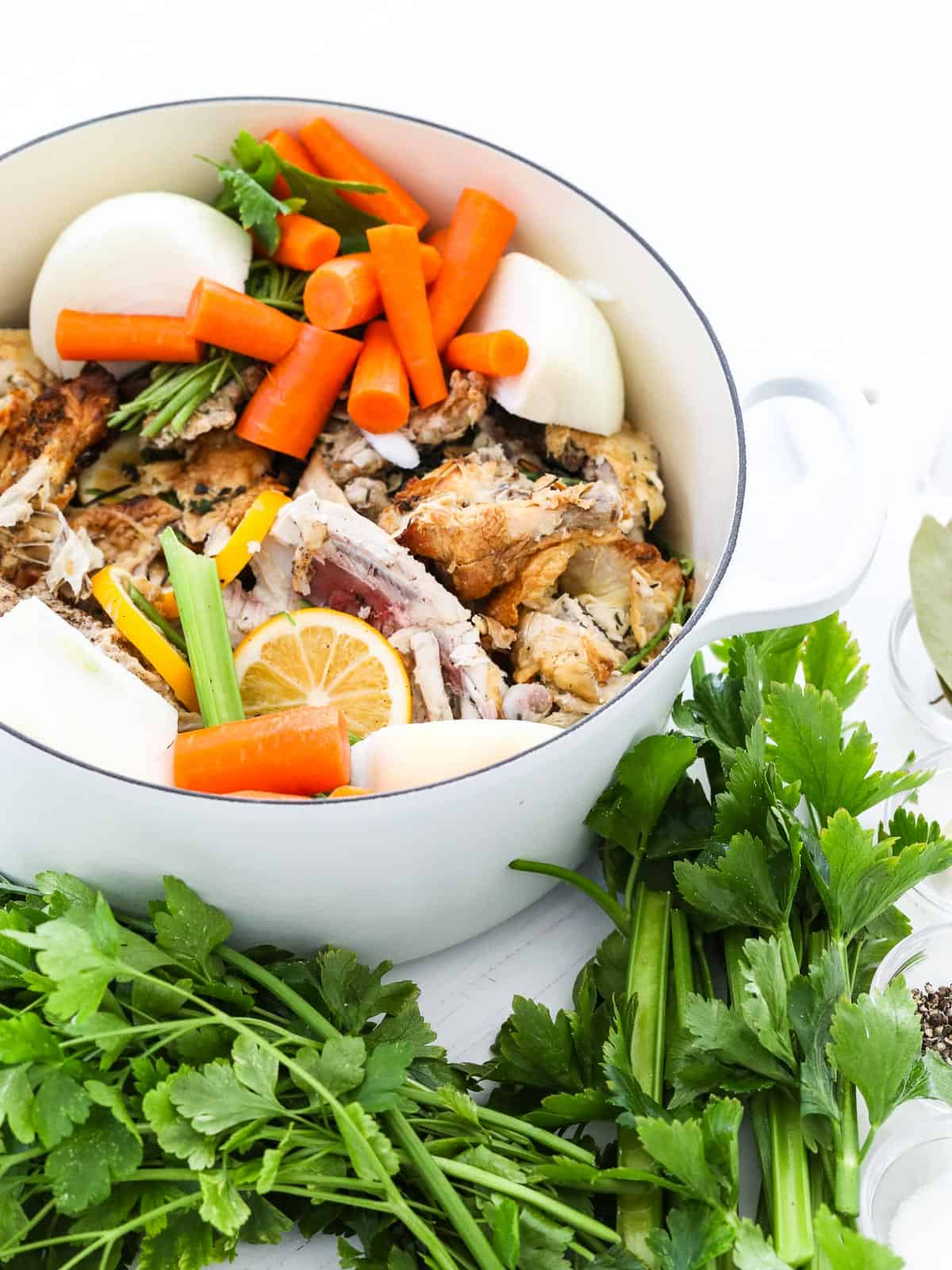 A large white cooking pot filled with ingredients to make chicken stock at home.