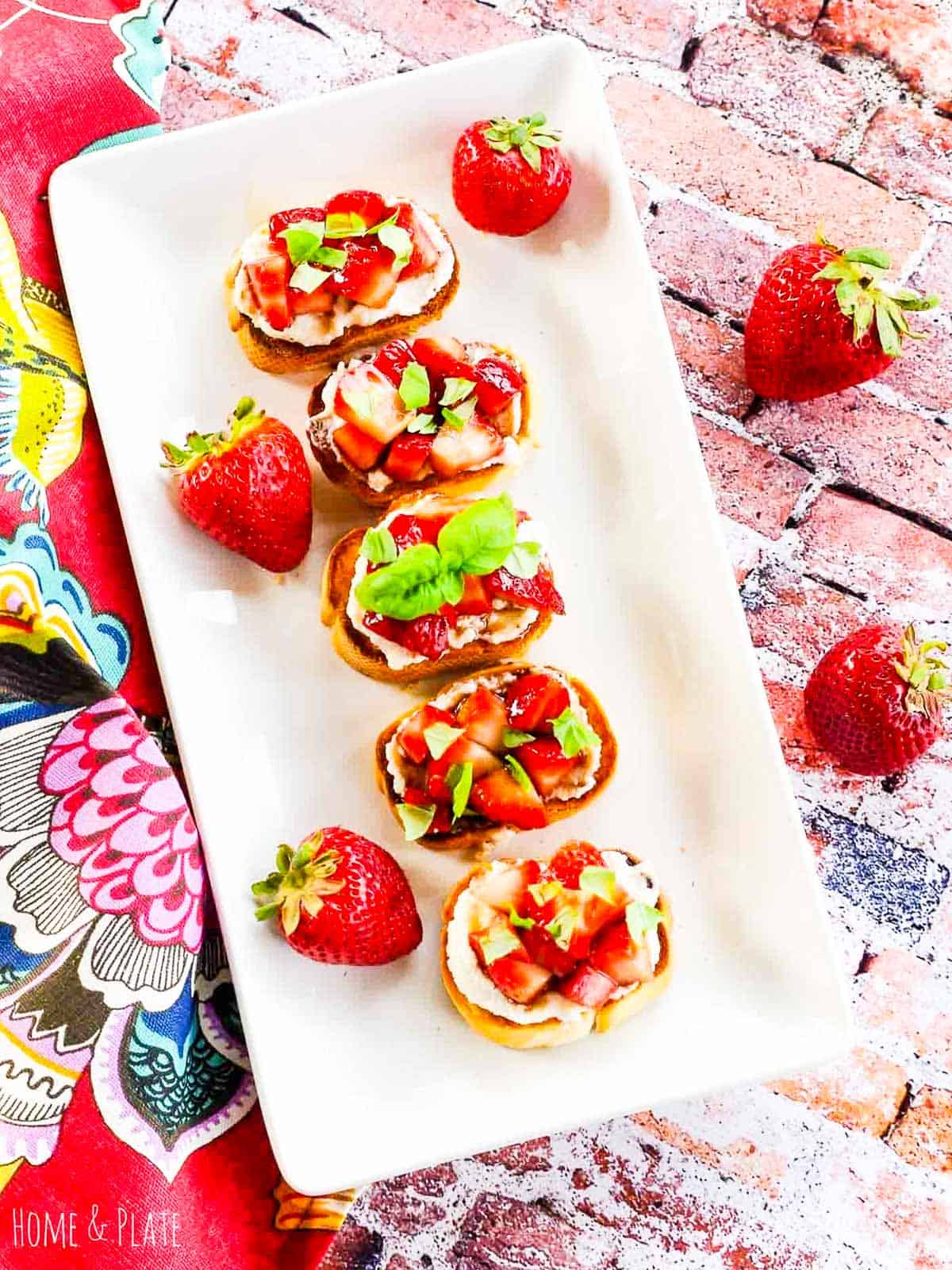 A white platter with strawberry topped crostini appetizer at a party.