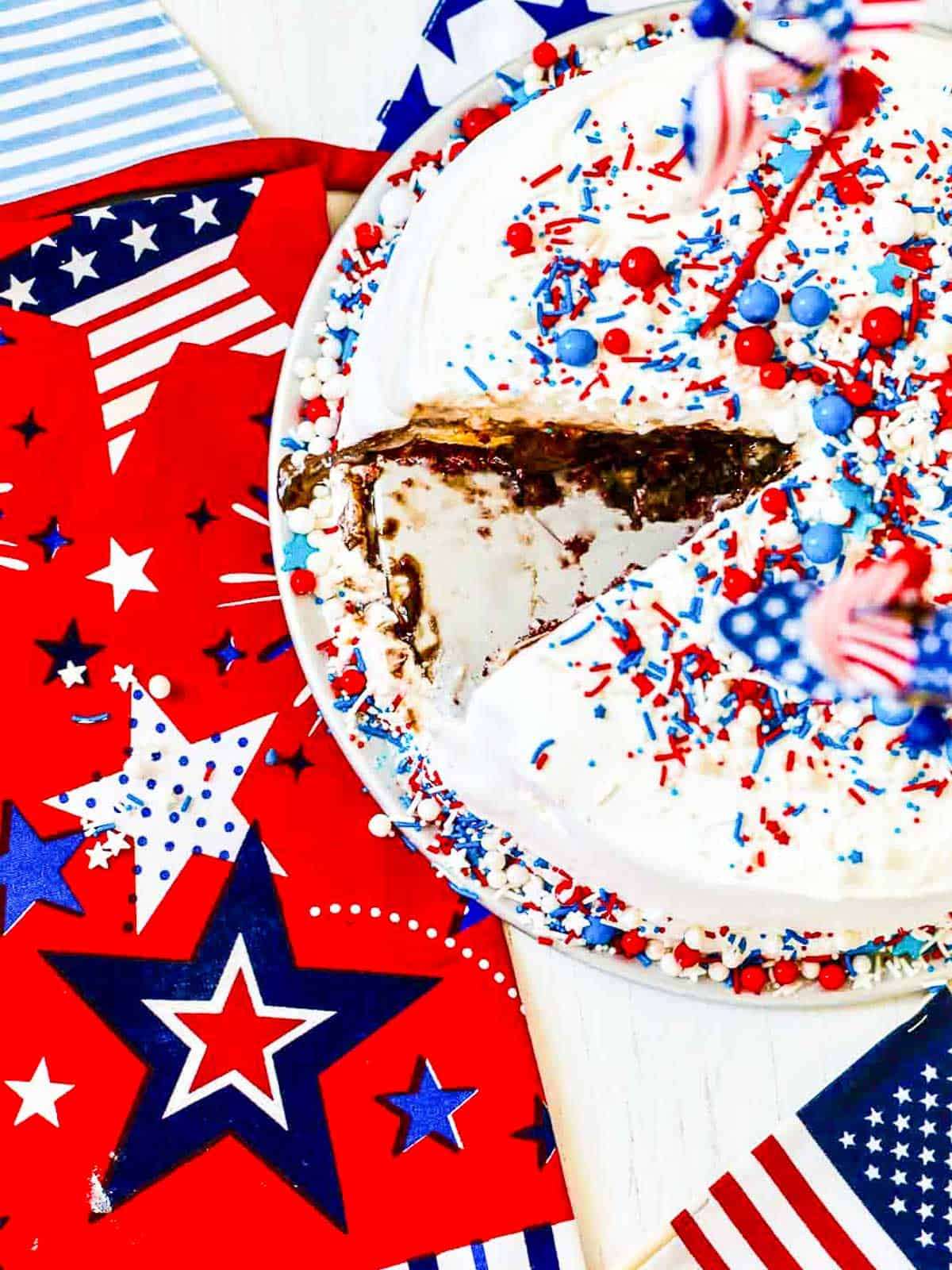 An ice cream cake for July 4th with a slice cut out of it on a patriotic red, white, and blue star tablecloth.