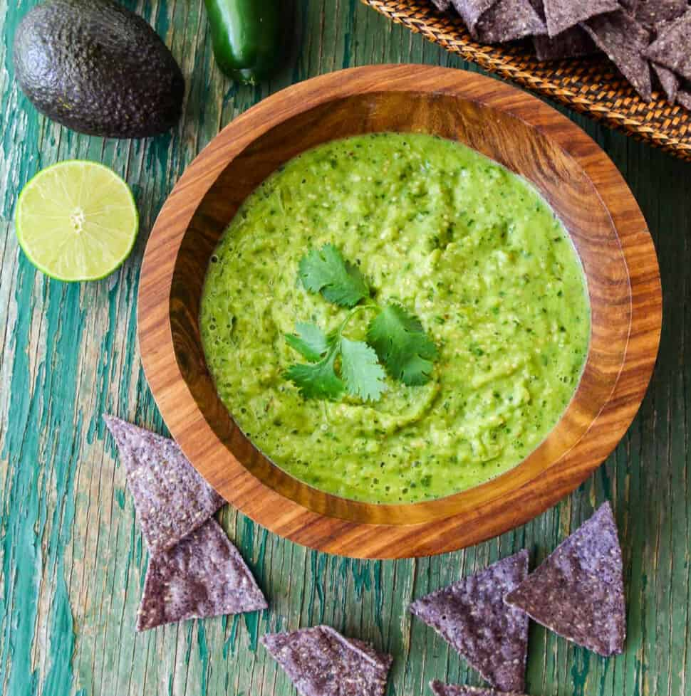 A wood bowl with green avocado salsa taco sauce and blue corn tortilla chips on the table.
