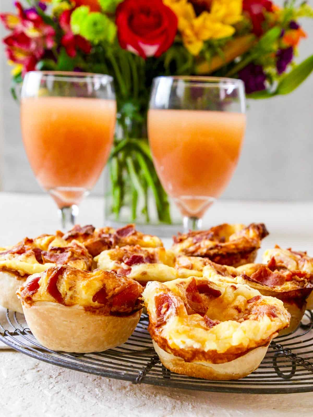 Two glasses of grapefruit juice with mini quiches and flowers in the background at brunch.