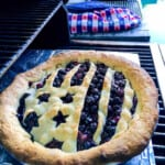 A blueberry pie that is baked outdoors on a grill with a flag shaped pie crust.