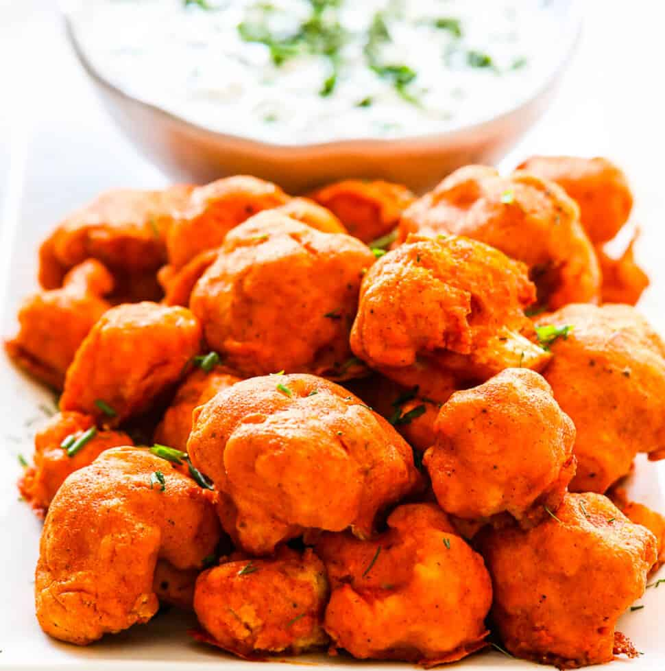 Baked Buffalo Cauliflower on a plate with ranch dip sprinkled with fresh herbs.