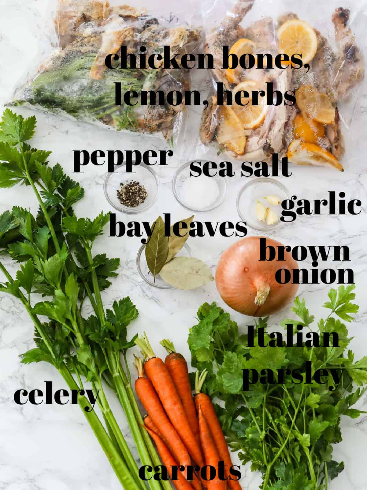 A table filled with ingredients to make a chicken stock recipe all labeled.
