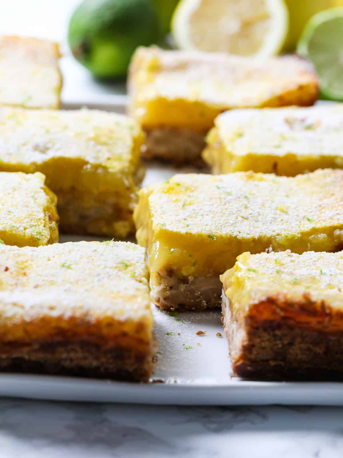 Large slice lemon bars dusted with powder sugar and lime zest on a white plate.