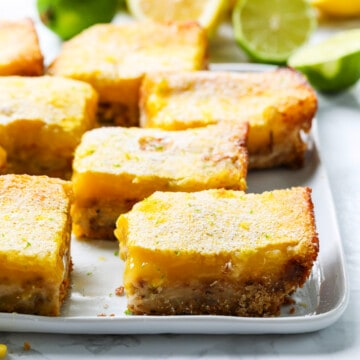 A white plate with large lemon bars cut into squares dusted with powder sugar.