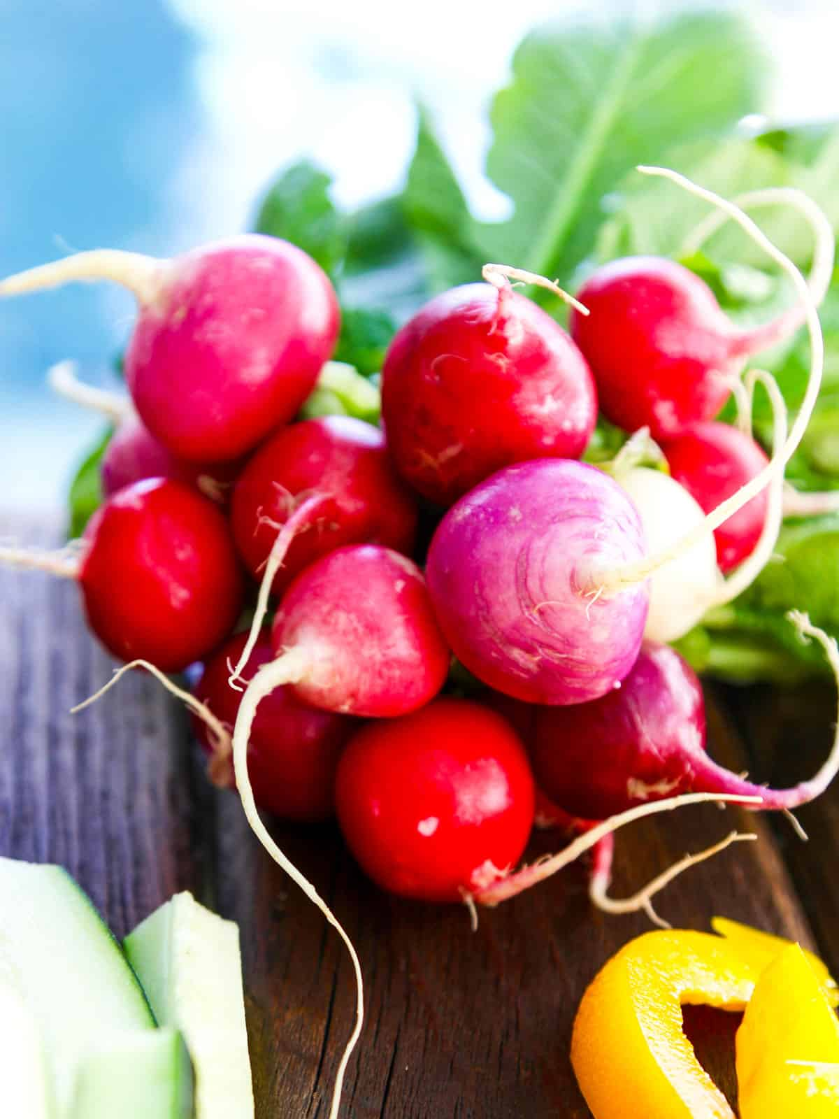 A bunch of bright red colorful radishes tied in a bundle on a board.