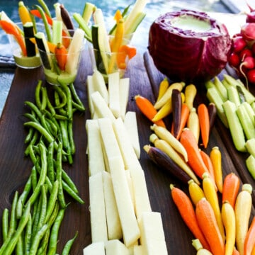 A cutting board with crudites and dip with bright colored vegetables cut into strips and sticks.