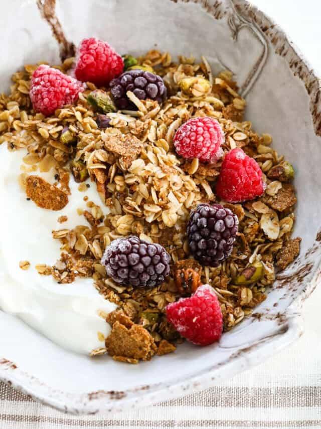 A handmade ceramic bowl filled with yogurt and topped with granola, raspberries, and black berries.