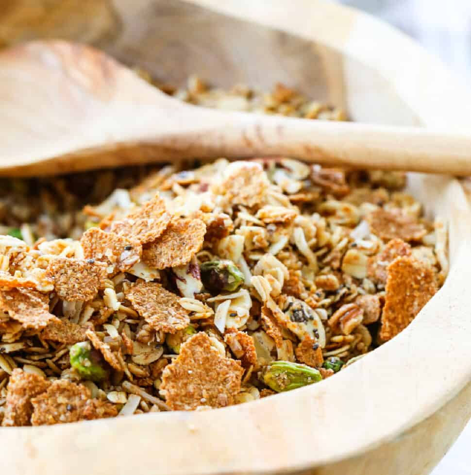 A wooden bowl filled with granola and a wooden spoon.