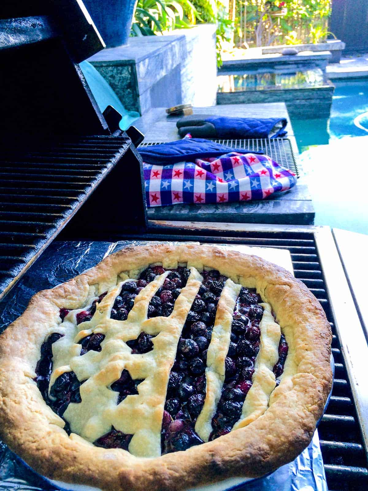 A blueberry pie with a flag crust baked on a grill.