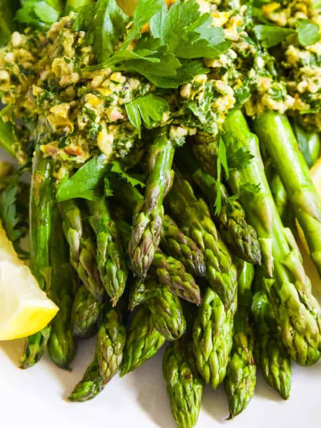A white plate filled with cooked asparagus topped with gremolata garnished with lemon wedges.