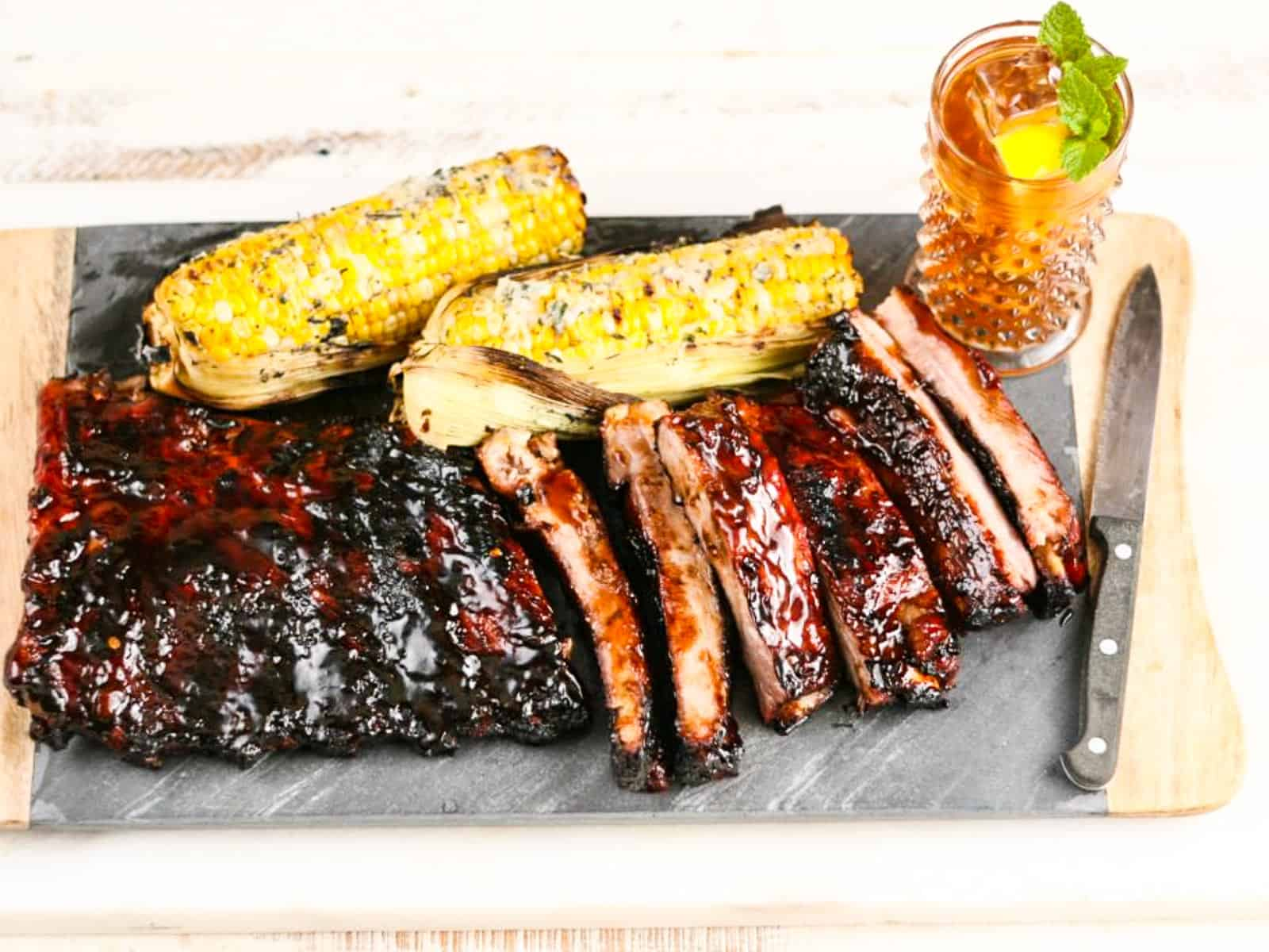 A pile of BBQ ribs with corn and sweet tea at a BBQ cookout.