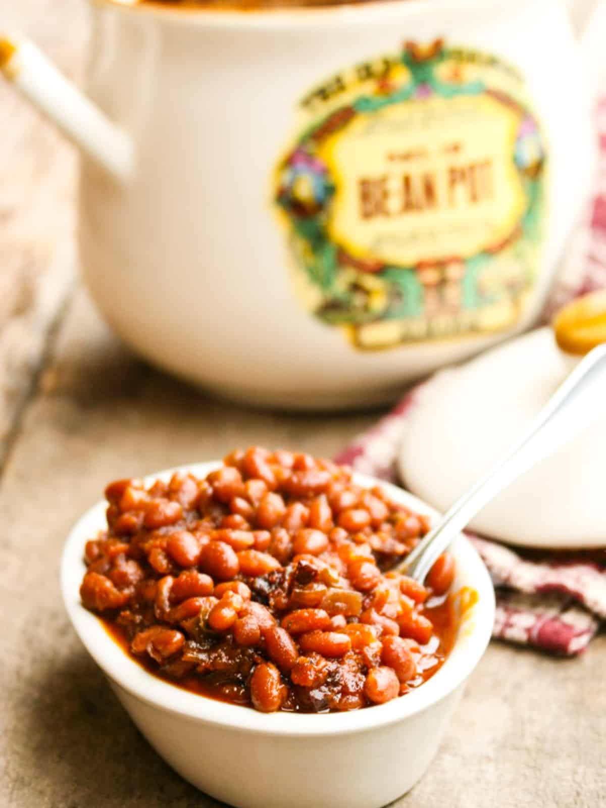 A small white bowl filled with baked beans with a bean pot in the background.