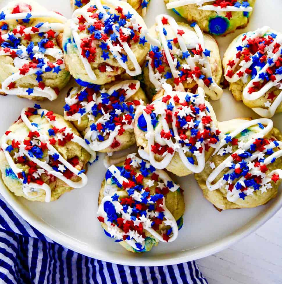 A white plate filled with July 4th red white and blue cookies with icing and star sprinkles.