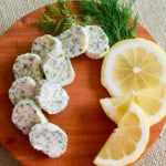 Small brown round cutting board with slices of lemon dill butter garnished with fresh lemon and dill.