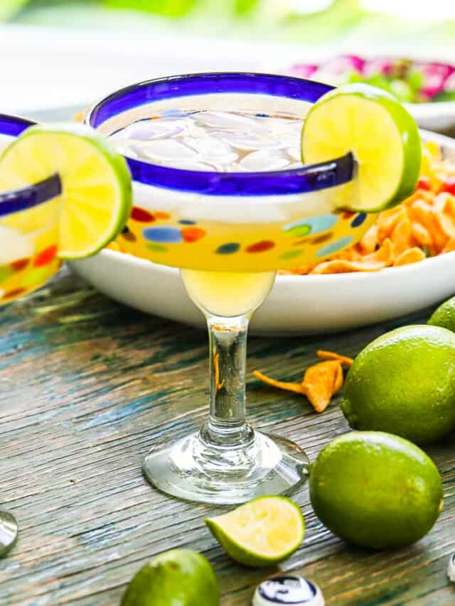 Blue rimmed margarita glasses with margaritas in them on ice cubes with sliced lime garnish.