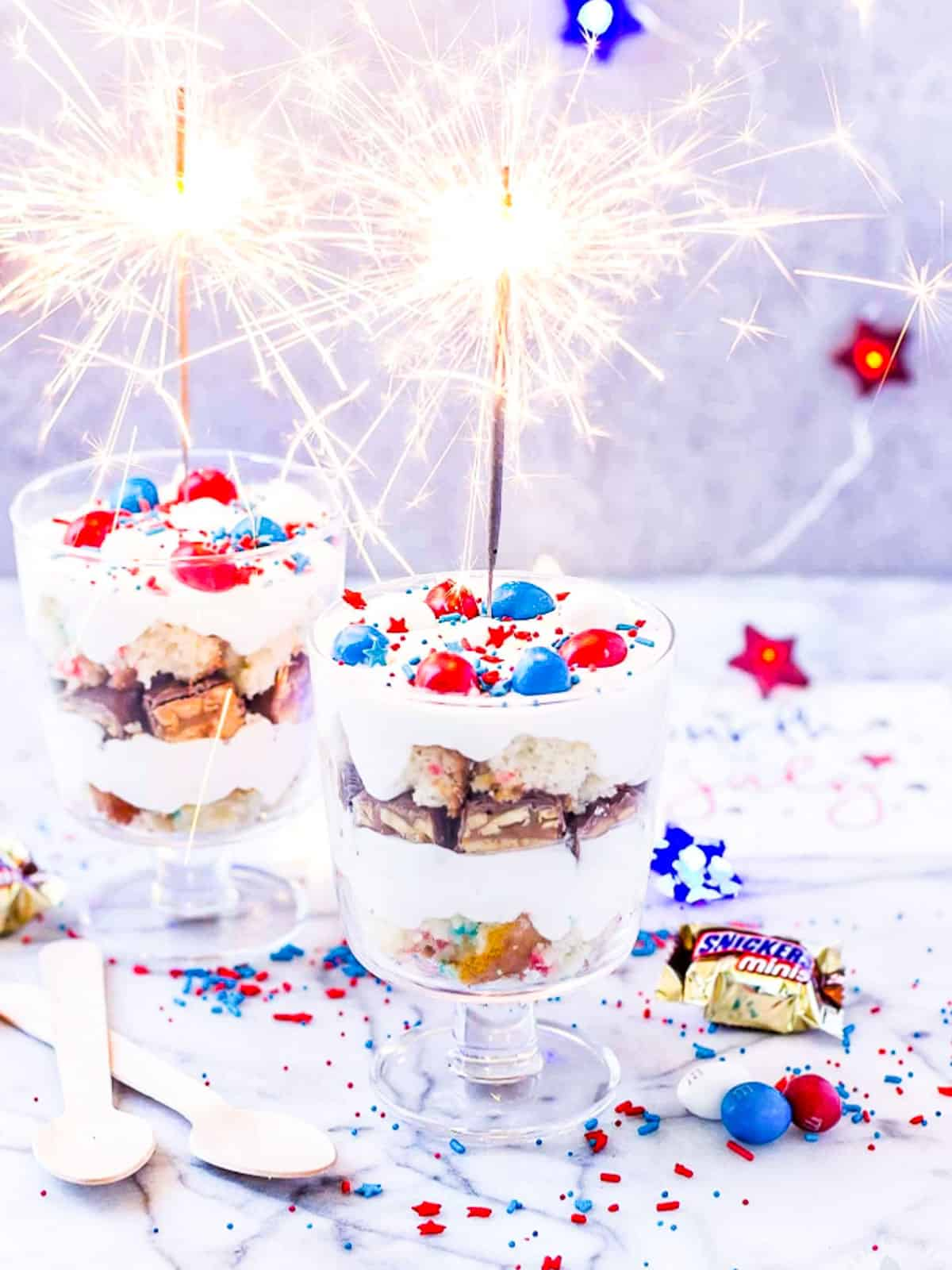 Small glass trifles filled with candy, whip cream, and July 4th sprinkles.