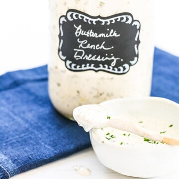 A large Mason jar filled with ranch dressing made at home with a small serving bowl and spoon.