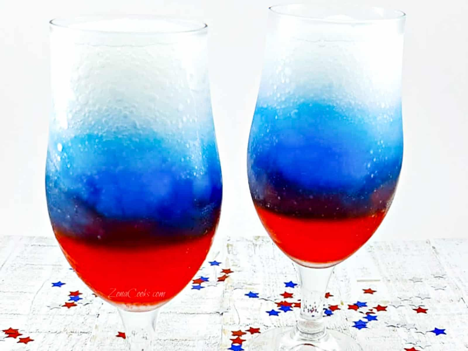 Two glasses of red white and blue drinks on ice in wine goblets.
