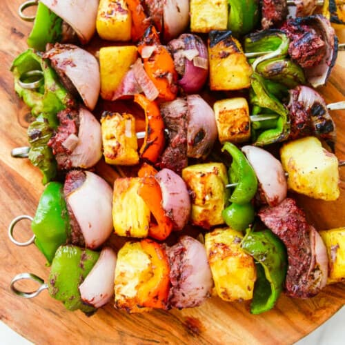 A wooden platter filled with Shish Kabob grilled skewers.