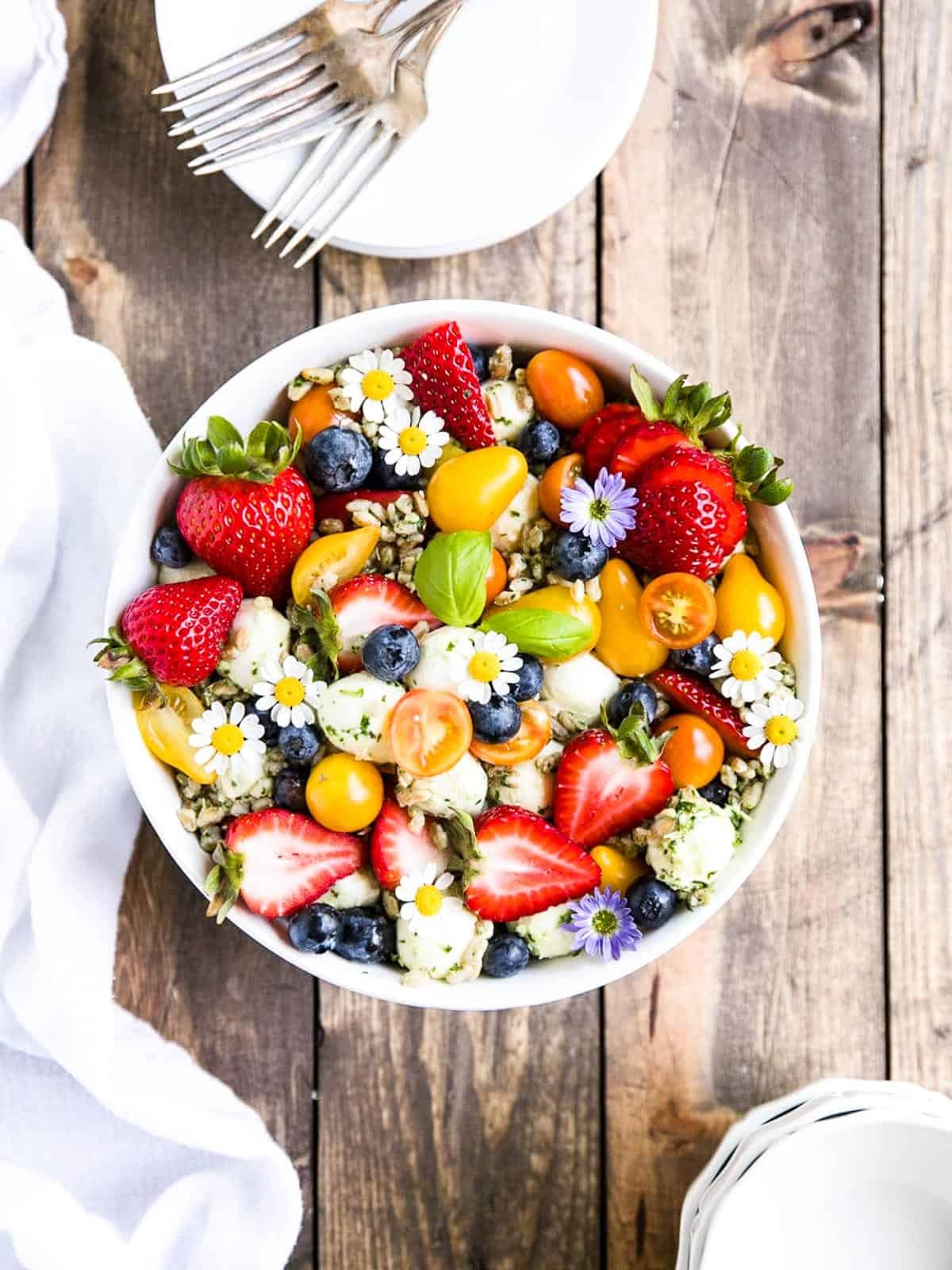 A strawberry, tomato summer salad garnished with little daisies.