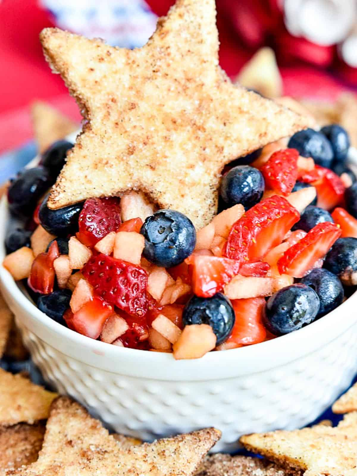 A white bowl with fruit salsa and a cinnamon cookie on top.