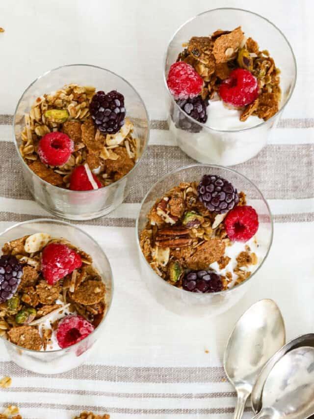 Four small yogurt parfaits made with yogurt, granola and berries.