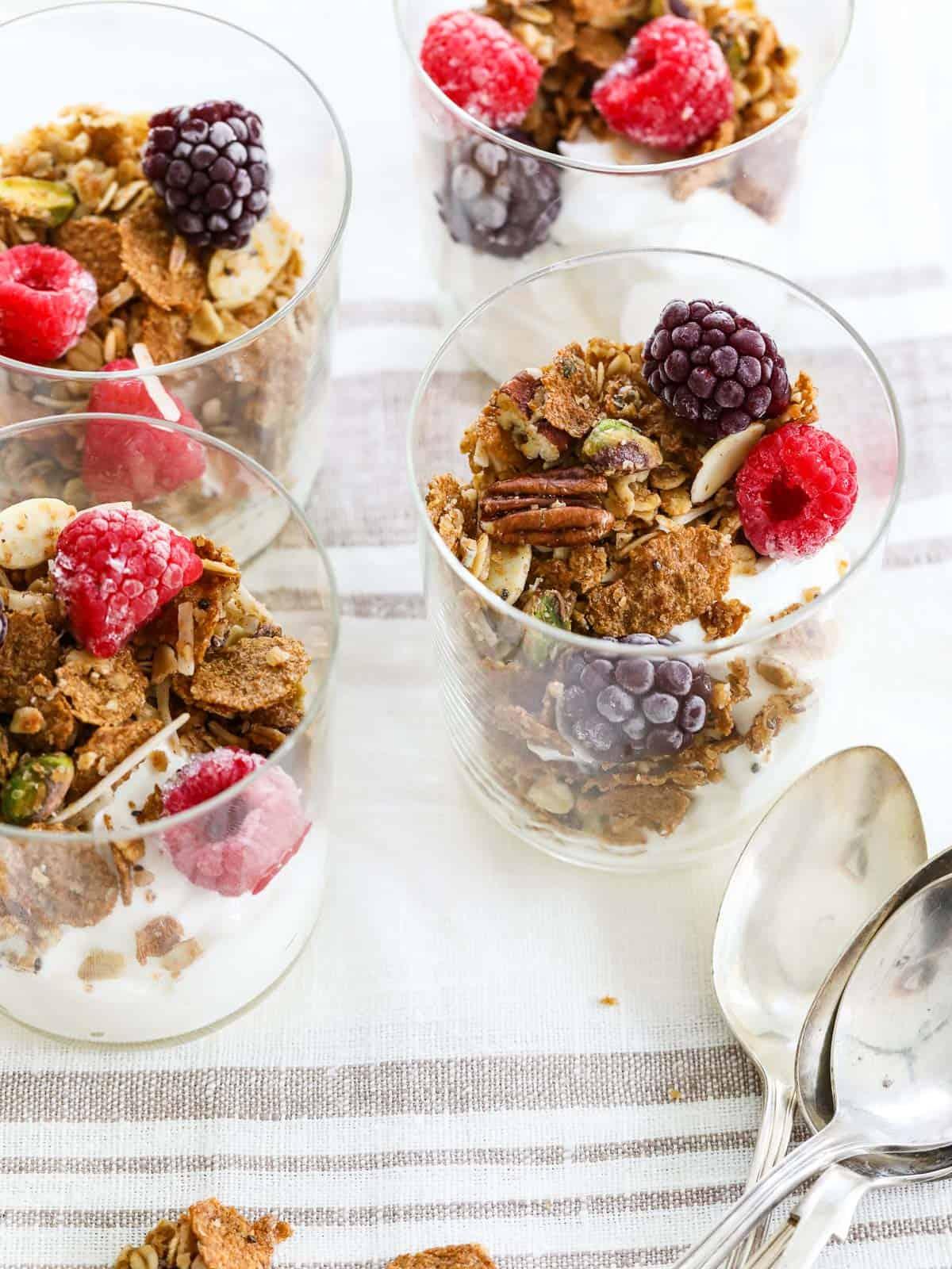 Four yogurt parfaits layered with yogurt, granola, and fresh raspberries and blackberries.