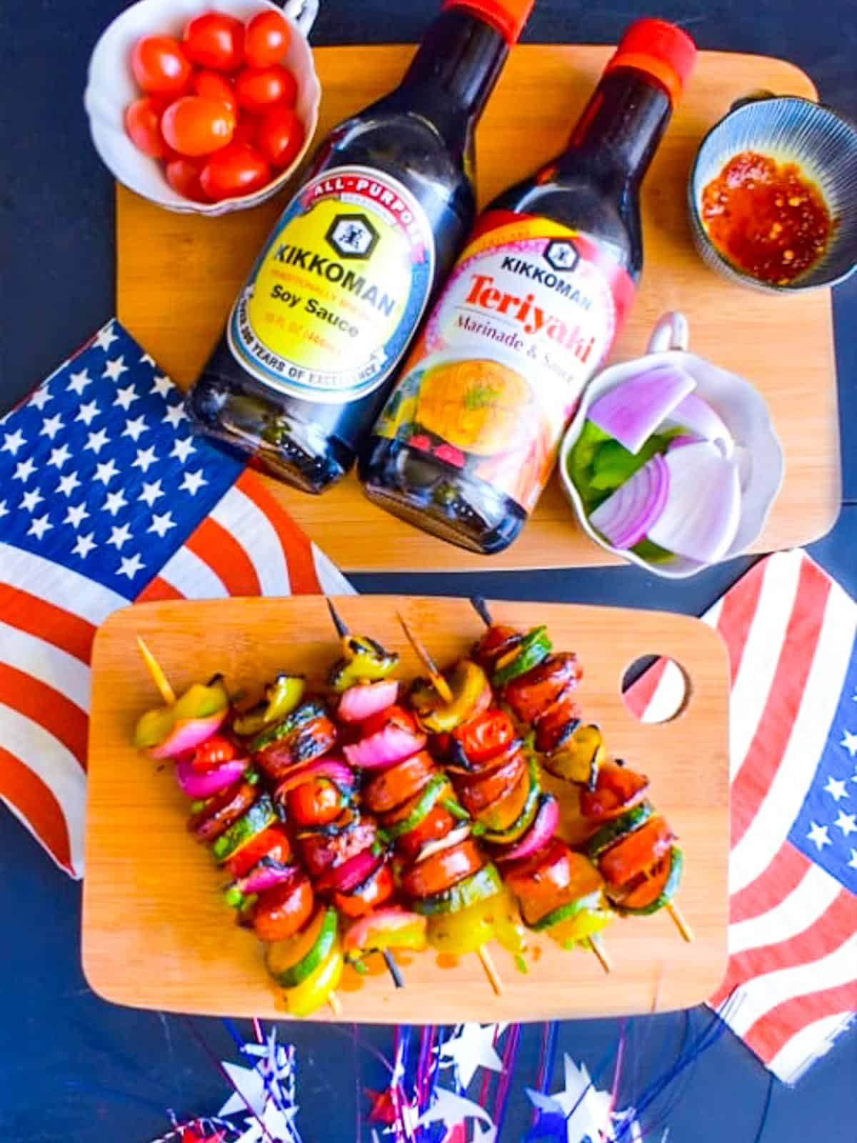 A cutting board with bright colored kebabs with vegetables and sausages at a July 4th party.