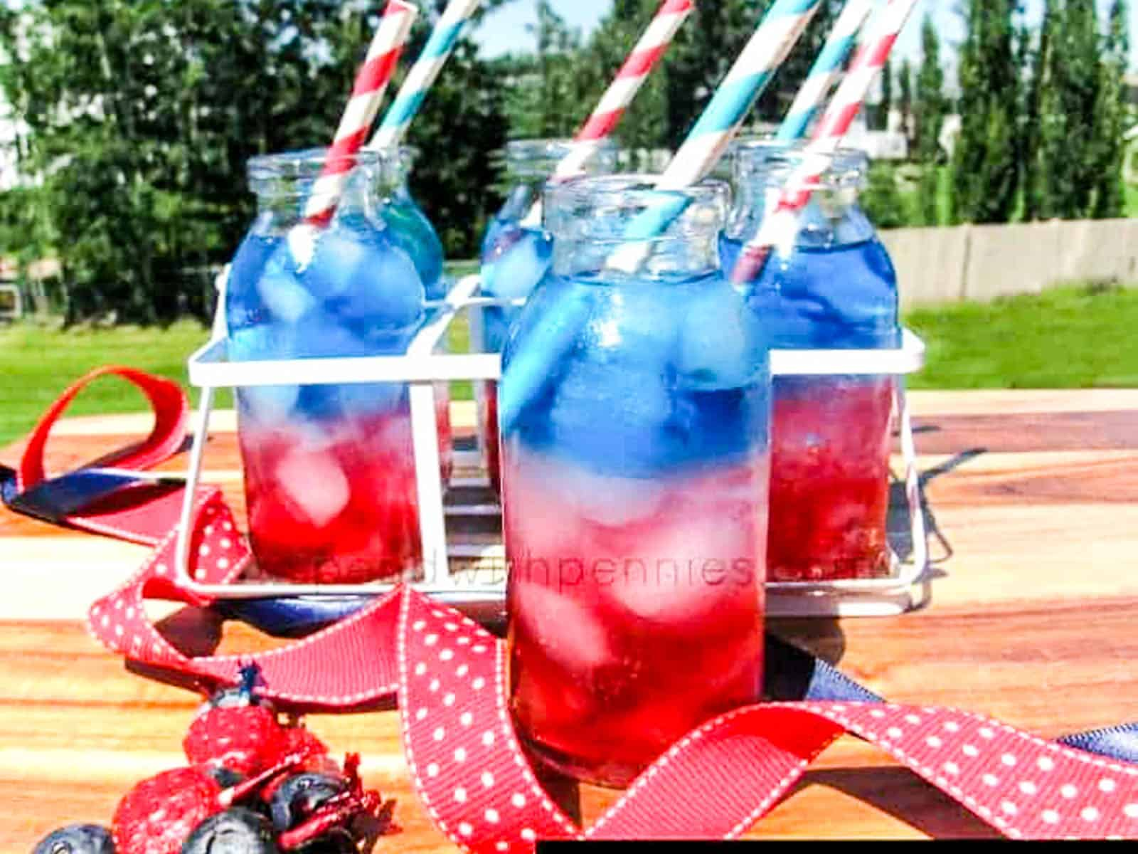 Four glasses of red white and blue drinks with straws at a July 4th party.