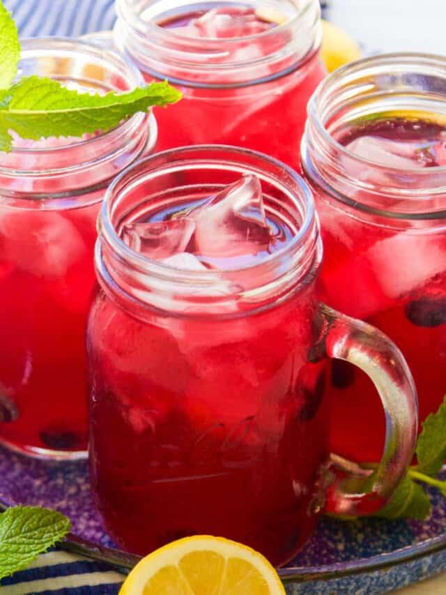 Mason jar handled glasses with blueberry lemonade garnished with blueberries, mint, and lemons halves.