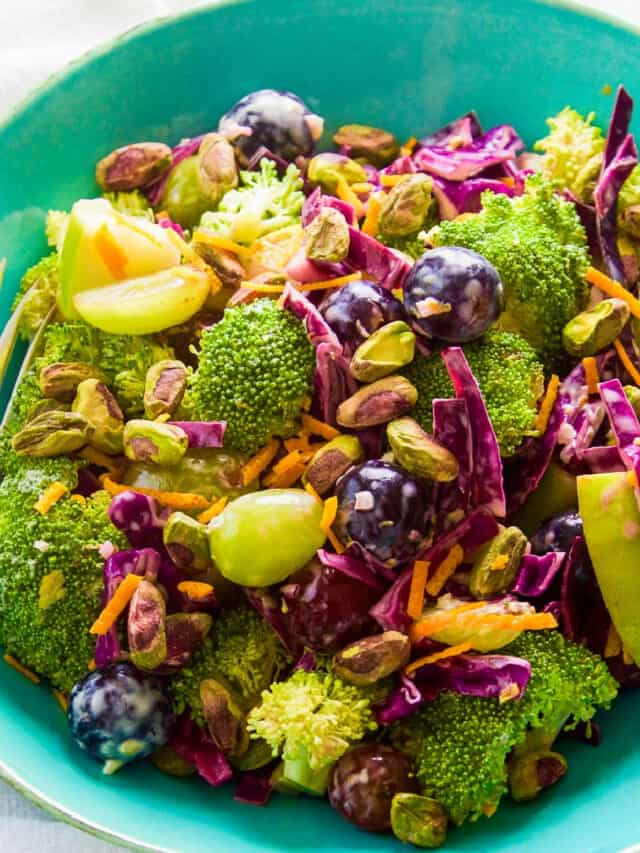 A turquoise salad bowl filled with broccoli salad with colorful grapes and pistachios.