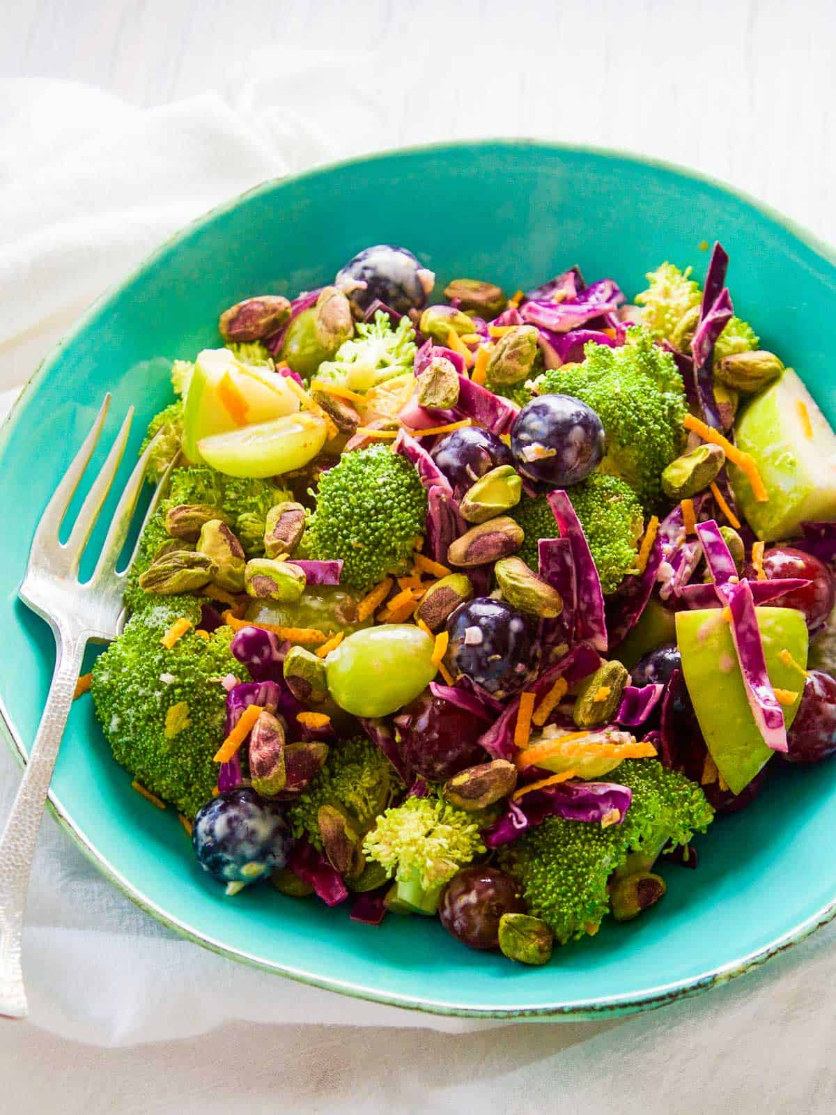 A turquoise blue bowl filled with colorful broccoli salad with pistachios and grapes.