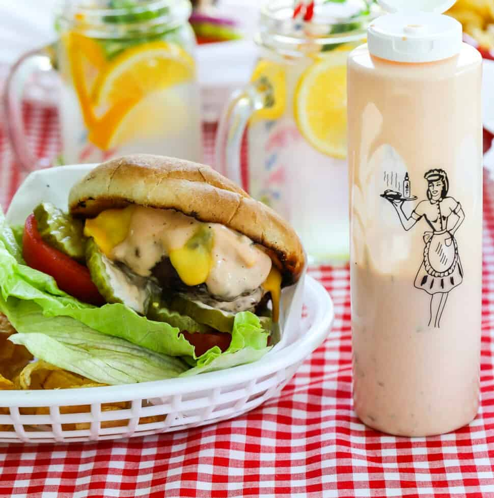 A messy grilled burger topped with lettuce, tomato, cheese, pickles and burger sauce in a basket with a bottle of burger sauce.