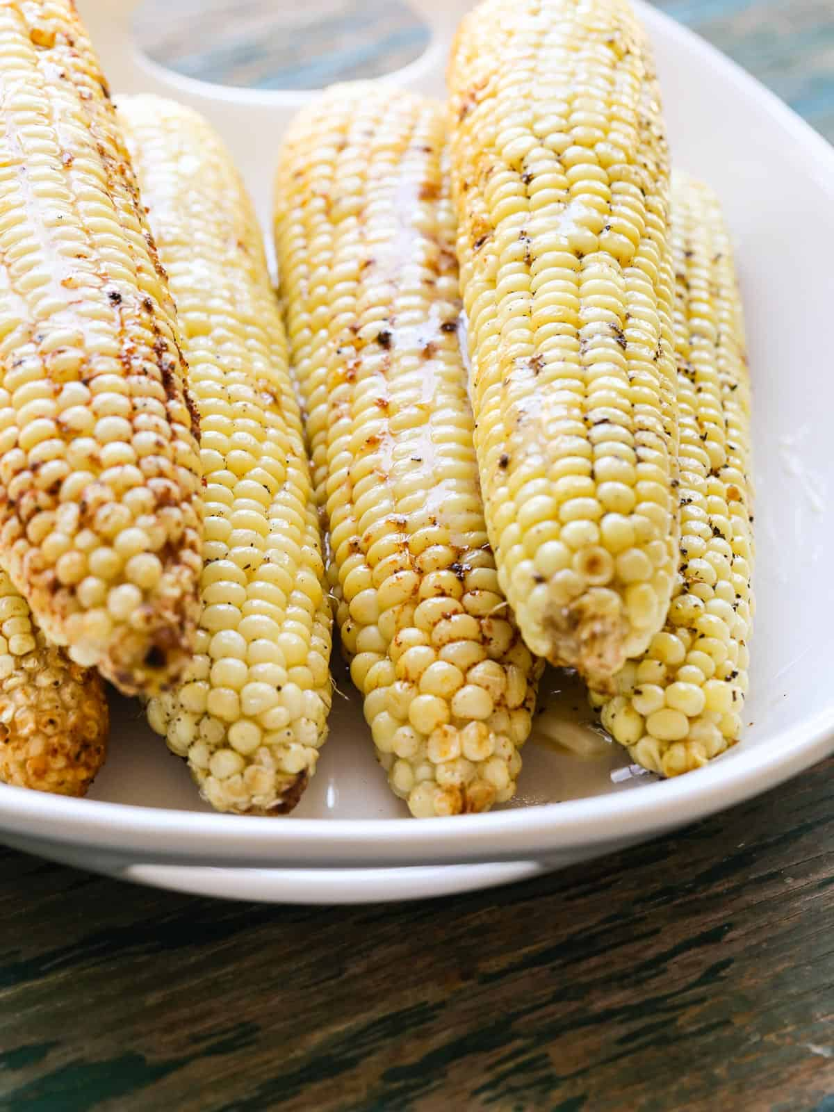 A white oval platter with grilled corn and melted butter on top.