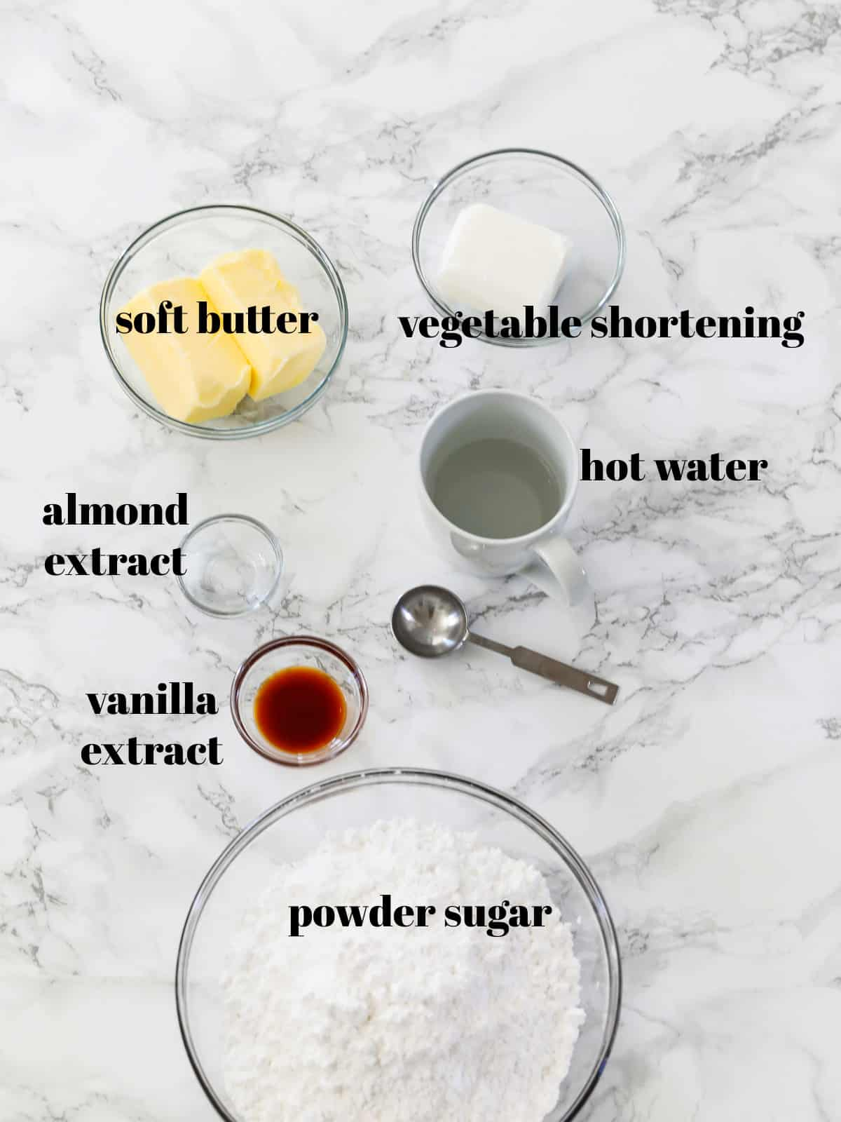 The ingredients to make cake frosting on a countertop labeled including powder sugar, butter, and shortening.